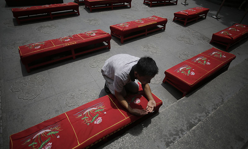 A man offers prayers to his deceased relatives on the Ghost Festival at Longhua Temple in Shanghai, China. The festival is to worship ancestors in China.—Photo by AP