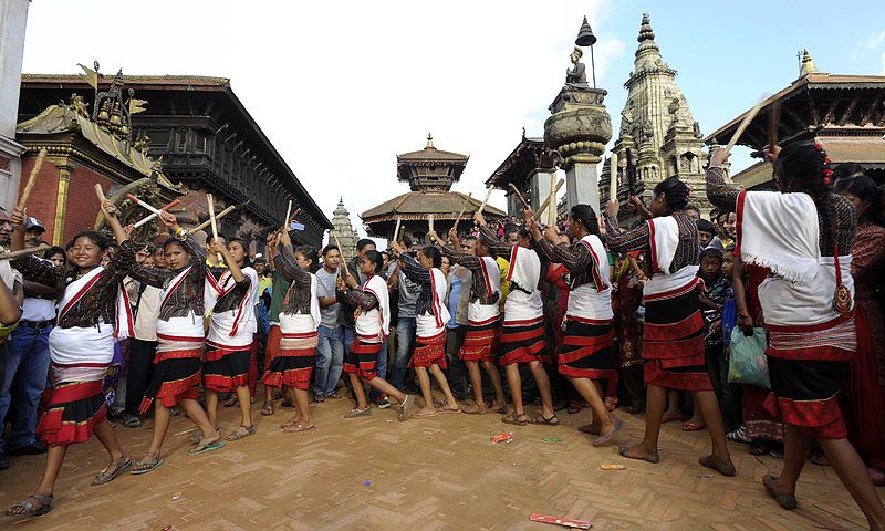 Nepalese youth dance with sticks as they take part in a procession for The Gai Jatra Cow Festival in Bhaktapur on the outskirts of Kathmandu.—Photo by AFP