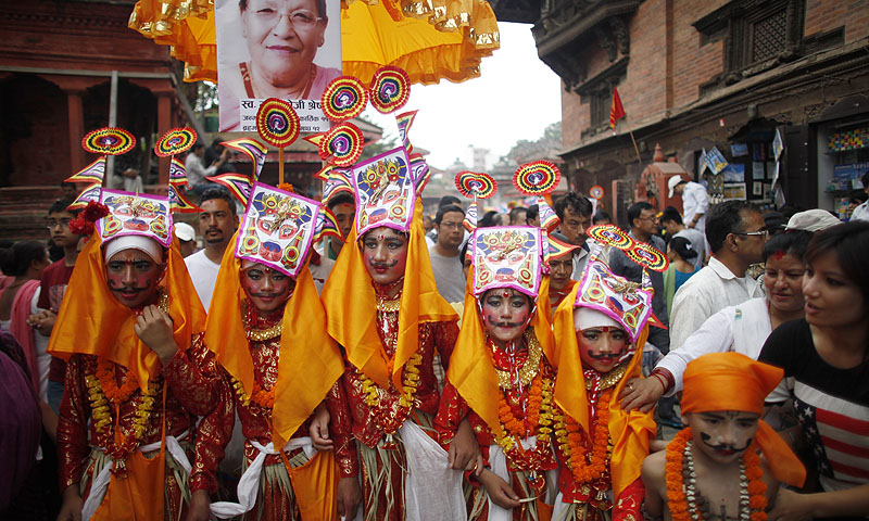 "A deceased person's photograph is displayed behind as Nepalese Hindu boys in festival attire line up during ""Gai Jatra,"" or Cow Festival, in Katmandu, Nepal. Members of Nepal's Newar Comunity celebrate the festival in memory of their family members who died the preceding year, believing that the cow will guide them in their journey to heaven.—Photo by AP"