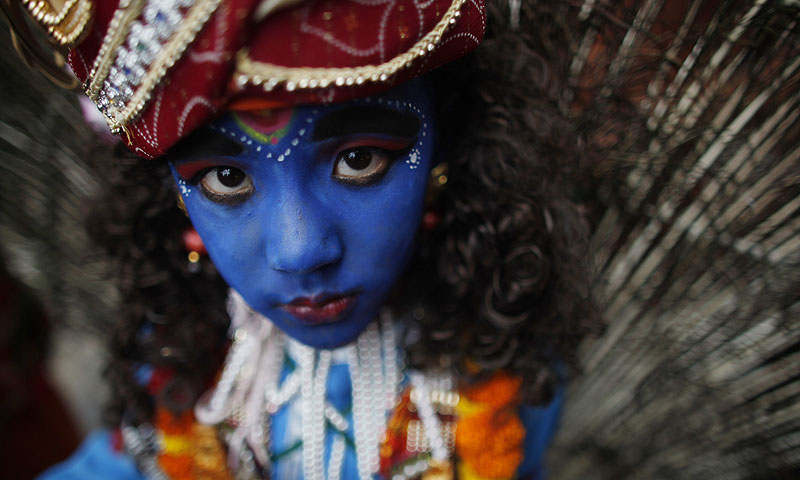 "A Nepalese Hindu boy dressed as Hindu deity Lord Krishna looks on during ""Gai Jatra,"" or Cow Festival, in Katmandu, Nepal. Members of Nepal's Newar Comunity celebrate the festival in memory of their family members who died the preceding year, believing that the cow will guide them in their journey to heaven.—Photo by AP"