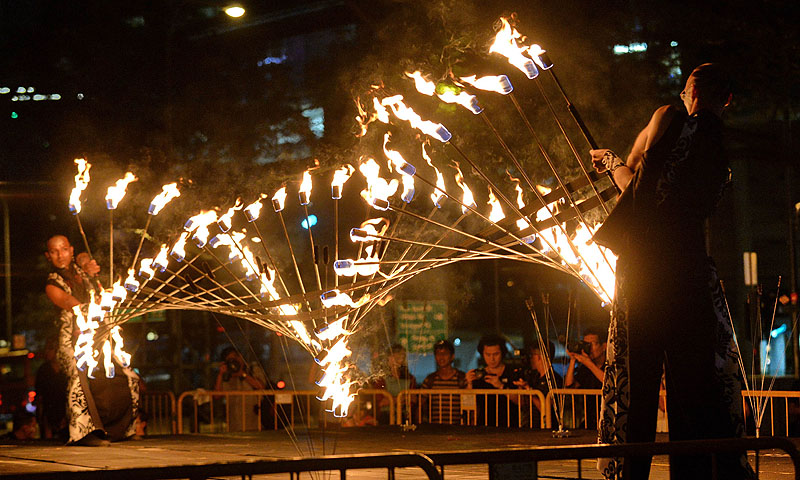 Performers from Starlight Alchemy perform a feat with fire during a media preview of the Singapore Night Festival.—Photo by AFP