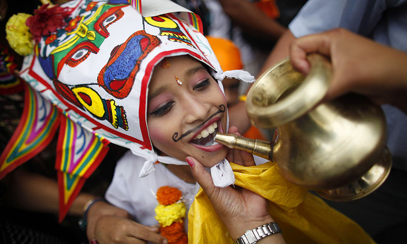 "A Nepalese Hindu boy dressed in festival attire is offered milk during ""Gai Jatra,"" or Cow Festival, in Katmandu, Nepal. Members of Nepal's Newar Comunity celebrate the festival in memory of their family members who died the preceding year, believing that the cow will guide them in their journey to heaven.—Photo by AP"