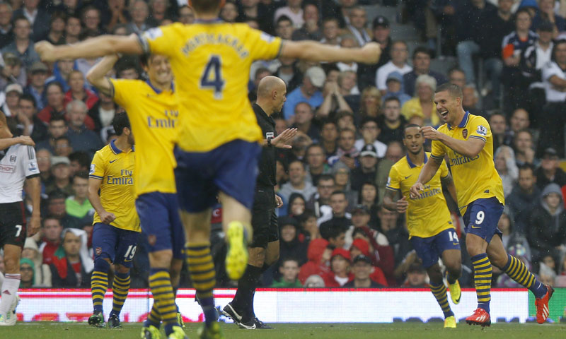 Arsenal's Lukas Podolski, right, celebrates his first goal against Fulham during their English Premier League soccer match at Craven Cottage, London, Saturday, Aug. 24, 2013. – AP Photo