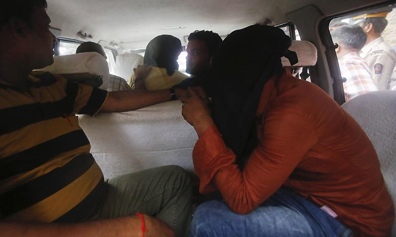 Two men (C and R, face covered), who were arrested in connection with the gang-rape of a photo journalist, sit in the police car as they leave a court in Mumbai August 25, 2013.— Photo by Reuters