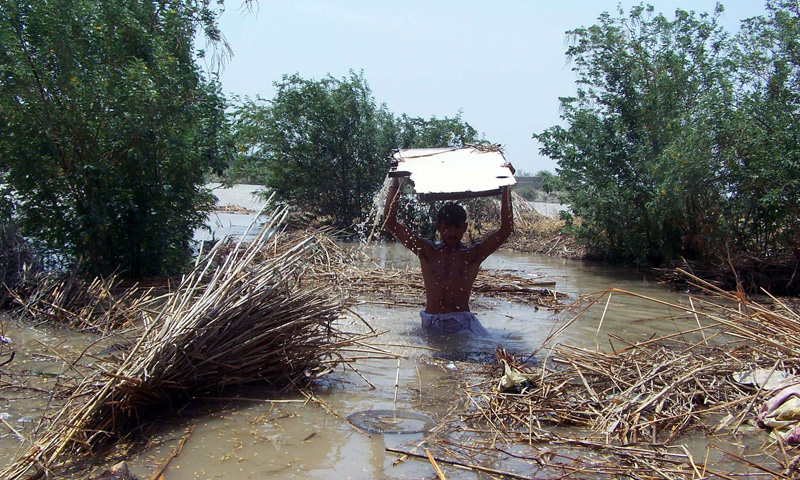 A boy wades through flood waters carrying household items in Hyderabad. – Photo by INP