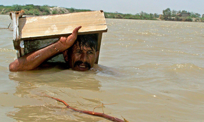 A man wades through chin deep water in Hyderabad after rains caused heavy flooding in the area. INP