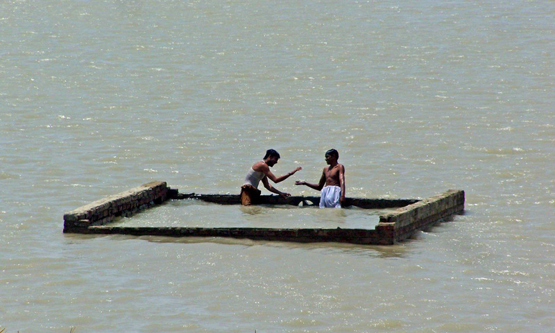 Boys standing on the roof of their house surrounded in flood water. – Photo by INP