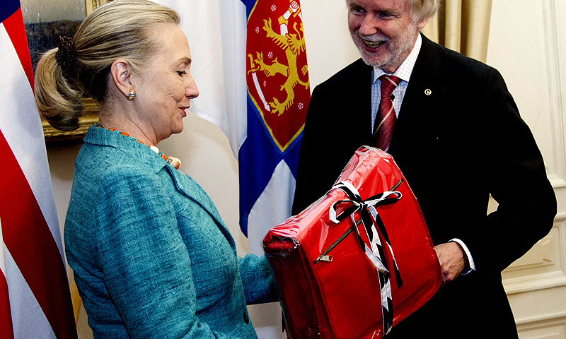 In this June 27, 2012 file-pool photo, then-Secretary of State Hillary Rodham Clinton receives a gift from Finnish Foreign Minister Erkki Tuomioja at the Government Banquet Hall in Helsinki, Finland. -Photo by AP