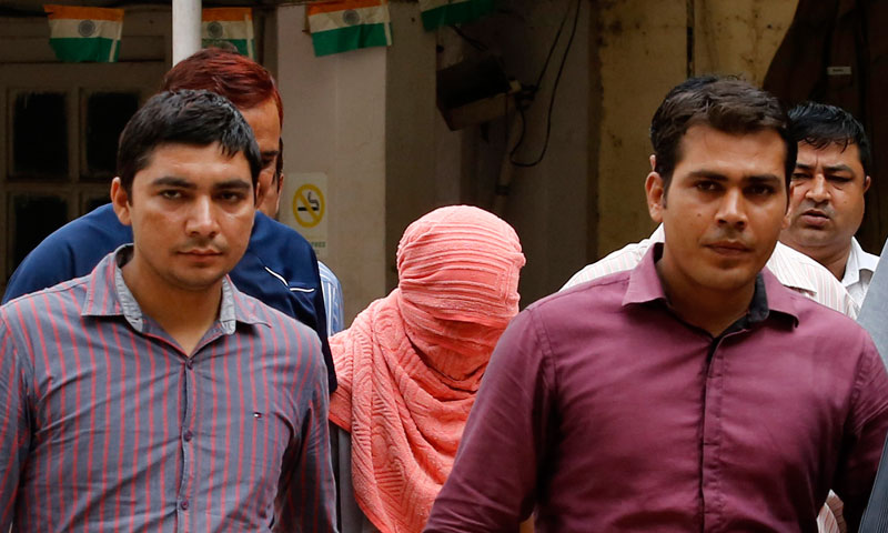 Plainclothes policemen escort an Indian teenager (head covered with towel) after he was sentenced at a juvenile court in New Delhi August 31, 2013. — Photo by Reuters