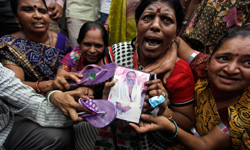 Supporters of India's ruling Congress party hold a photograph of godman Asaram Bapu and beat it with footwear during a protest in Ahmadabad, India, Saturday, Aug. 31, 2013. — Photo by AP