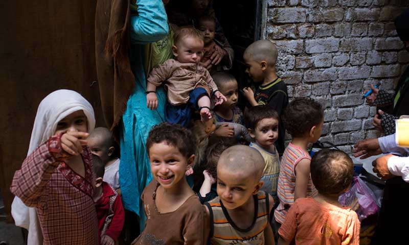 In this Aug 27, 2013 photo, children of four families living in a house wait to be immunised against polio in Rawalpindi. — Photo by AP