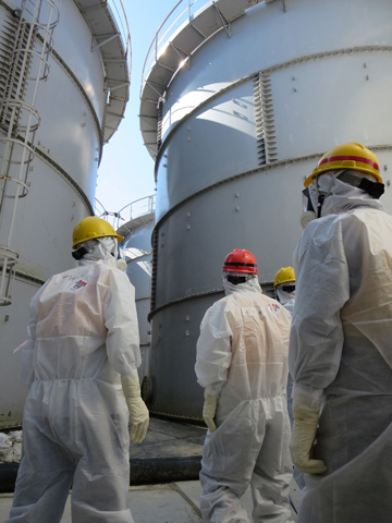This handout picture taken by Tokyo electric Power Co. (TEPCO) on August 26, 2013 and received on September 1, 2013 shows Japanese Economy, Trade and Industry Minister Toshimitsu Motegi (C-red helmet) inspecting contamination water tanks at TEPCO's Fukushima Dai-ichi nuclear power plant in the town of Okuma, Fukushima prefecture.  TEPCO said on August 31 it had found new radiation hotspots near tanks storing toxic water, with one reading peaking at 1,800 millisieverts per hour - a potentially lethal dose. — AFP Pho