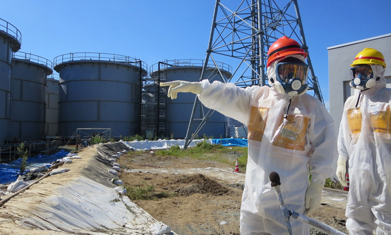 This handout picture taken by Tokyo Electric Power Co. (TEPCO) on August 26, 2013 and received on September 1, 2013 shows Japanese Economy, Trade and Industry Minister Toshimitsu Motegi (2nd R-red helmet) inspecting contamination water tanks at TEPCO's Fukushima Dai-ichi nuclear power plant in the town of Okuma, Fukushima prefecture. TEPCO said on August 31 it had found new radiation hotspots near tanks storing toxic water, with one reading peaking at 1,800 millisieverts per hour - a potentially lethal dose. — AFP
