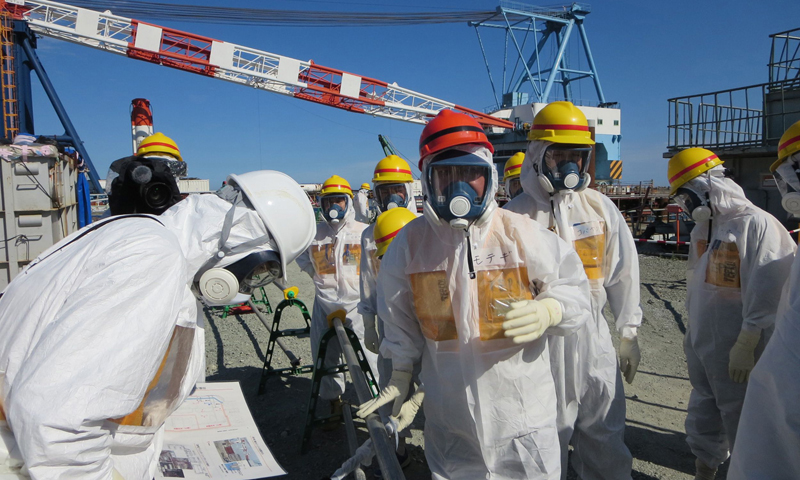 This handout picture taken by Tokyo Electric Power Co. (TEPCO) on August 26, 2013 and received on September 1, 2013 shows Japanese Economy, Trade and Industry Minister Toshimitsu Motegi (C-red helmet) inspecting TEPCO's Fukushima Dai-ichi nuclear power plant in the town of Okuma, Fukushima prefecture.  TEPCO said on August 31 it had found new radiation hotspots near tanks storing toxic water, with one reading peaking at 1,800 millisieverts per hour - a potentially lethal dose.  — AFP Photo