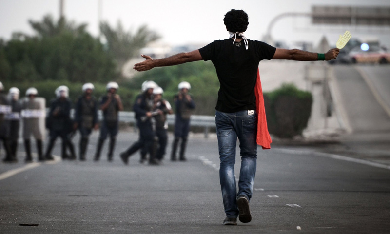 A Bahraini protester stands facing riot police during clashes following the funeral of Sadeq Sabt, in the village of North Sehla, west of Manama, on September 1, 2013. Sabt, 22, died of his injuries after he was hit by a vehicle during a protest a month before. The Sunni-ruled kingdom has been rocked by sporadic violence since its security forces crushed a month of Arab Spring-inspired democracy protests by Shiites in 2011.