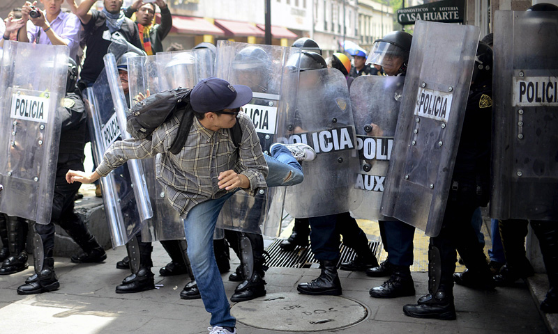 Demonstrators clash with riot police during a protest against President Enrique Pena Nieto's reform agenda, on September 1, 2013, in Mexico City. Police launched tear gas at protestors who threw rocks and firebombs in Mexico City on Sunday, leaving two officers injured and at least four people arrested during the demonstration.