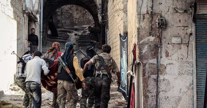 a group of Free Syrian Army fighters carry a wounded comrade to cover in the town of Harem, Syria - File Photo/AP