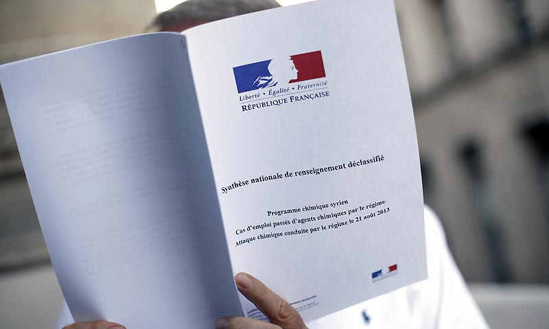 A picture taken on September 2, 2013 in Paris shows a man reading a synthesis note of France's various intelligence services which establishes, according to Paris, that the regime of Syrian president Bashar al-Assad was behind a deadly chemical attack on August 21. — Photo by AFP