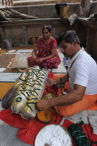 An Indian Jain devotee prepares a coating to be placed on a Jain God idol for decoration at the Hutheesing Jain temple on the first day of Parushan Parva in Ahmedabad.