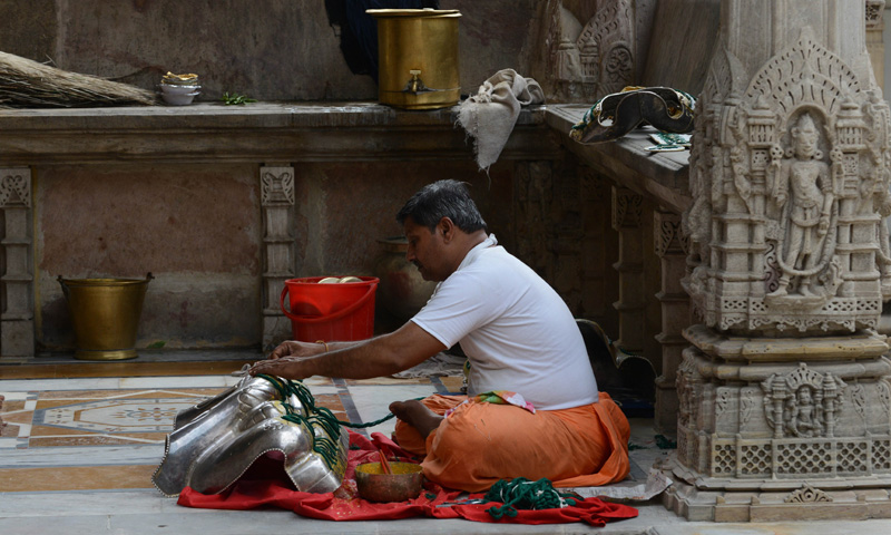 An Indian Jain devotee prepares a coating to be placed on a Jain God idol for decoration.