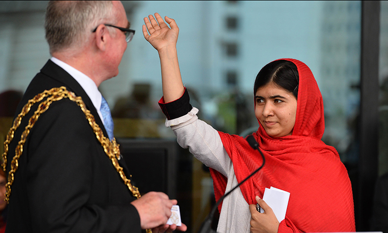 Malala Yousafzai (R), the 16-year-old Pakistani advocate for girls education, waves as she officially opens The Library of Birmingham. - AFP Photo