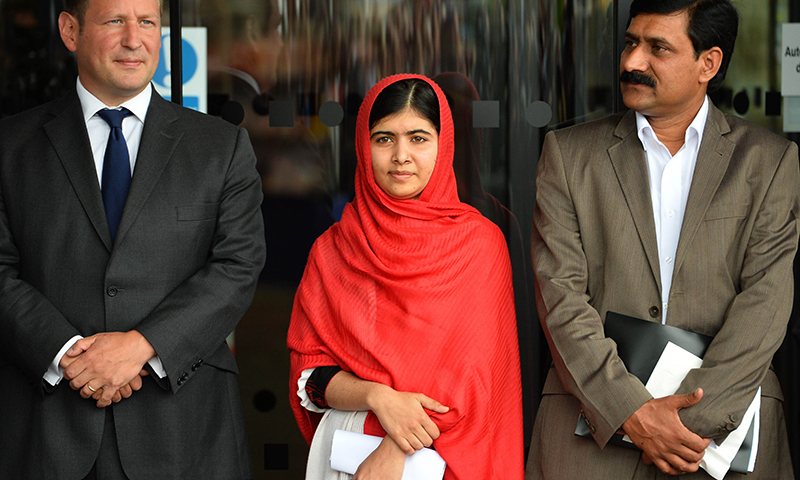 Malala Yousafzai stands next to her father Ziauddin Yousafzai (R) before officially opening The Library of Birmingham in Birmingham. - Photo by AFP