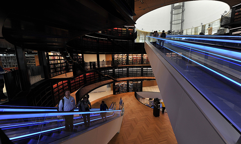 Members of the press tour the inside of The Library of Birmingham on its opening day in Birmingham central England. - Photo by AFP