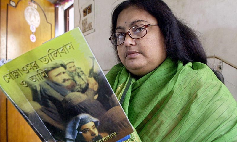 "In this photograph taken on March 6, 2003, Indian author Sushmita Banerjee holds one of her Bengali language novels ""Mollah Omar Taliban O Aami"" (Mollah Omar, Taliban and Me) in Kolkata. -AFP Photo"