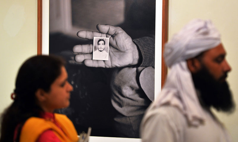Visitors walk past a photograph showing a relative holding the portrait of a prisoner currently under detention by the US at the Bagram prison in Afghanistan. -Photo by AFP