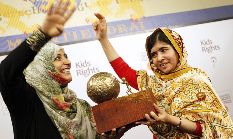 Malala Yousafzai (R) receives a trophy from Yemeni Civil Rights activist and 2011 Nobel Peace Prize winner Tawakkul Karman after being honored with the International Children's Peace Prize at the Ridderzaal in the Hague, the Netherlands, on September 6, 2013. – AFP Photo