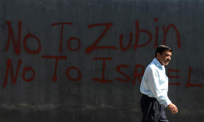 A Kashmiri walks past graffiti against the Ehaas-Kashmir music concert featuring conductor Zubin Mehta in Srinagar on September 6, 2013.— Photo by AFP
