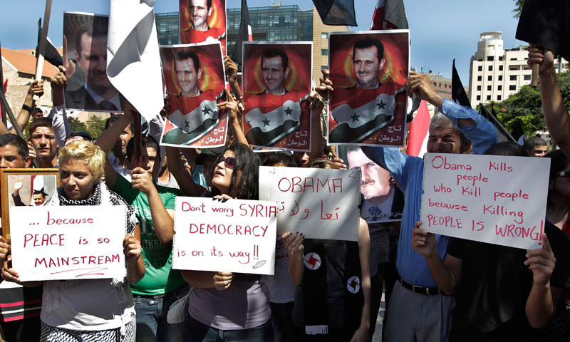Members of the Syrian Social Nationalist Party chant slogans as they hold portraits of Syrian President Bashar Assad, during a demonstration against a possible military strike in Syria, in front of the United Nations headquarters, in Beirut, Lebanon, Sunday, Sept. 8, 2013. - Photo by AP