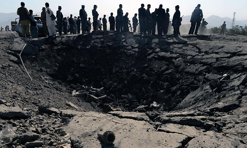 Afghan policemen and villagers look on near a crater at the scene of suicide attack in Maidan Shar, the capital city of Wardak province south of Kabul on September 8, 2013. — Photo by AFP