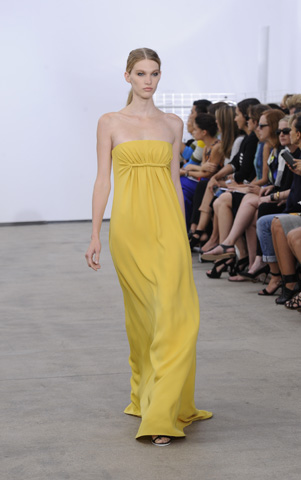 A model walks the runway at the Derek Lam fashion show wearing a soft yellow tube dress. – Photo by AFP