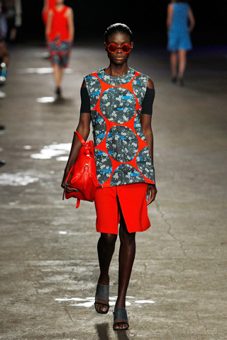 A model displays a red and floral ensemble with match red bag and shades. – Photo by AFP