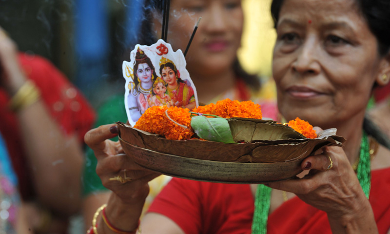 Indian Hindu Nepali devotees offer prayers to the Hindu god of destruction Lord Shiva as they celebrate the Teej festival in Siliguri on September 8, 2013. – Photo by AFP