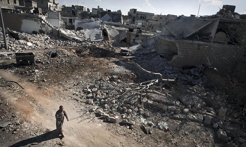 A man walks through a destroyed residential area of the Syrian city of Saraqib, southwest of Aleppo, on September 9, 2013, following repeated airstrikes by government forces' fighter jets. US President Barack Obama and his Russian counterpart Vladimir Putin discussed the idea of placing Syrian chemical weapons under international control at last week's G20 summit in Saint Petersburg, Putin's spokesman said on September 10, 2013. — Photo by AFP