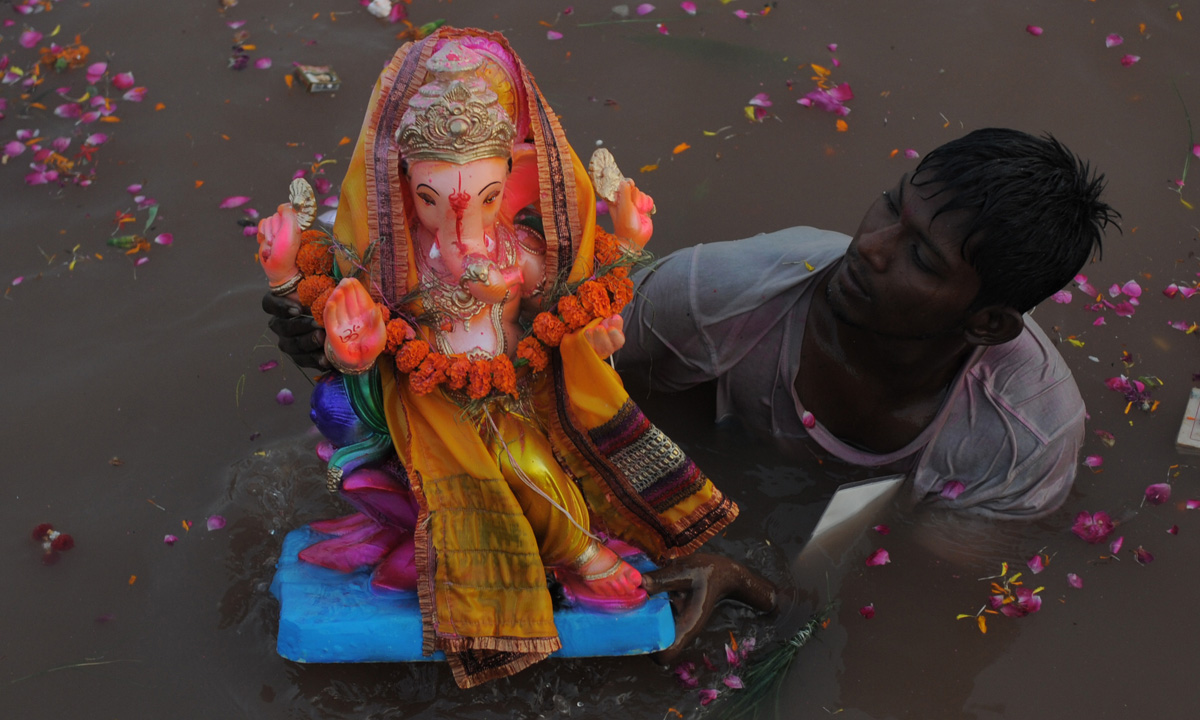 An Indian Hindu volunteer lowers an idol of Lord Ganesha into an artificial pond, dug for the ongoing Ganesh Chathurthi festival to help control pollution and waste, along the banks of the Sabarmati river in Ahmedabad. – Photo by AFP