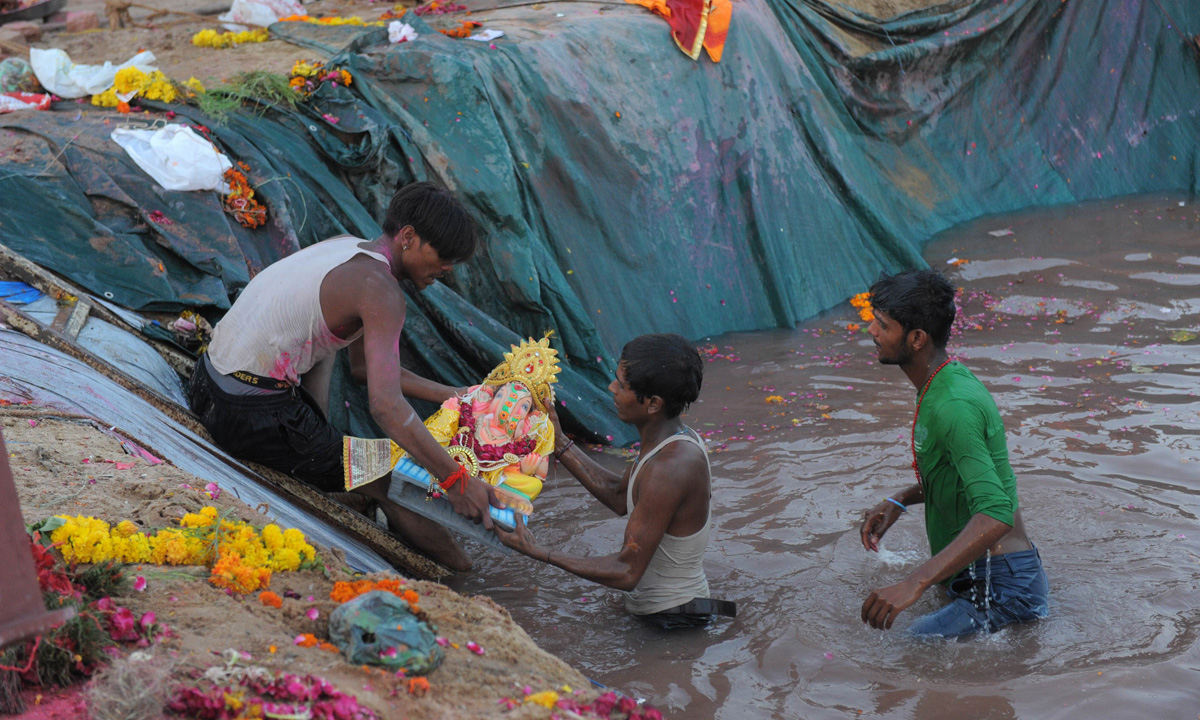 Indian Hindu volunteers lower an idol of Lord Ganesha into an artificial pond, dug for the ongoing Ganesh Chathurthi festival to help control pollution and waste, along the banks of the Sabarmati river in Ahmedabad. – Photo by AFP