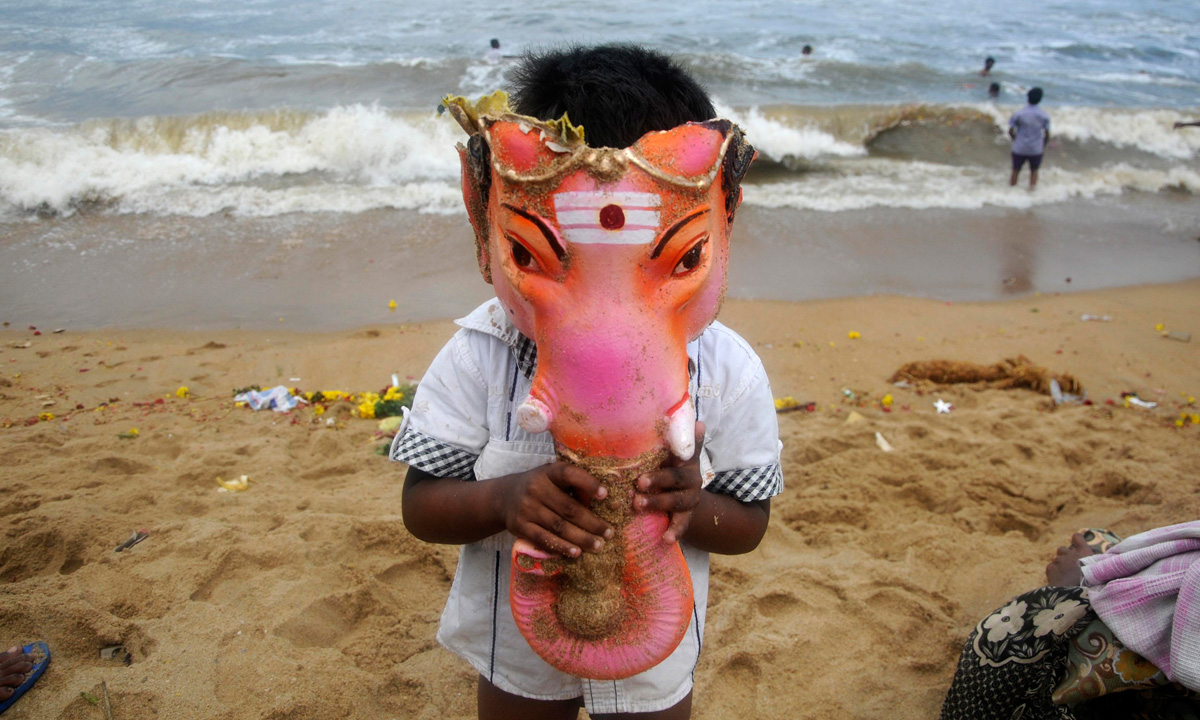 A boy wears the head of an idol of the Hindu god Ganesh, the deity of prosperity, during idol immersion ceremony of the ten-day-long Ganesh Chaturthi festival. – Photo by Reuters