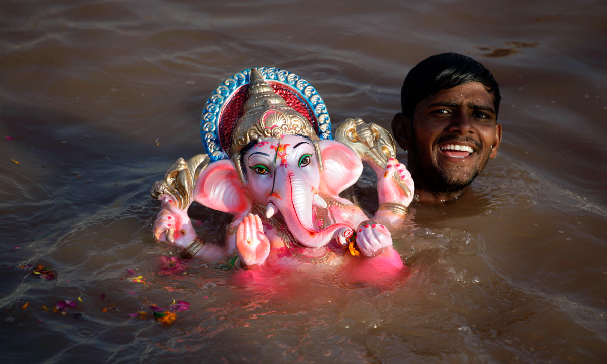 A volunteer smiles as he immerses an idol of elephant-headed Hindu god Ganesha in an artificial pond, specially set up for the immersion of idols to prevent pollution in the river Sabarmati, in Ahmadabad. – Photo by AP