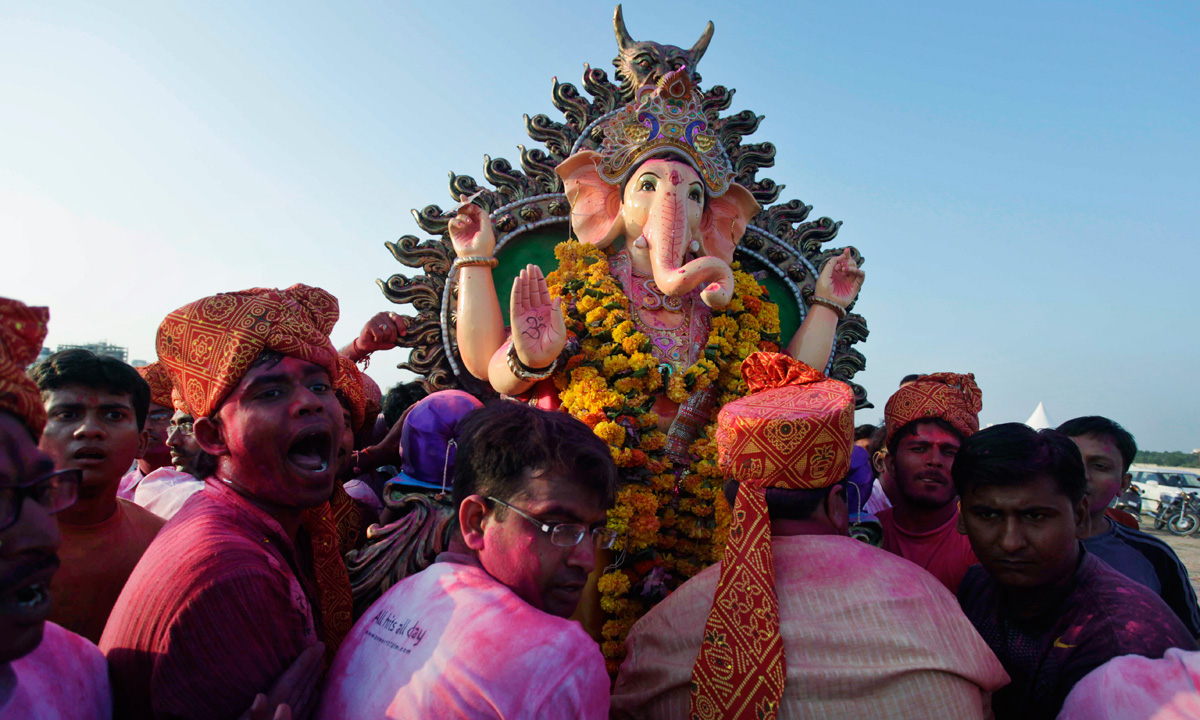 Worshippers carry an idol of elephant-headed Hindu god Ganesha for immersion in an artificial pond, specially set up for the immersion of idols to prevent pollution in the river Sabarmati, in Ahmadabad. – Photo by AP