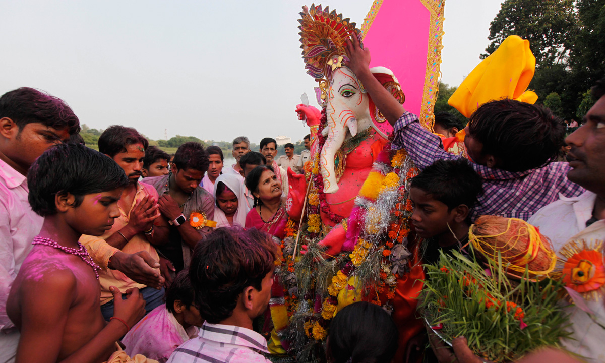 Indian devotees offer prayers as they prepare to immerse an idol of elephant-headed Hindu god, Ganesha in the Gomati River, during Ganesh Chaturthi festival celebrations in Lucknow. – Photo by AP