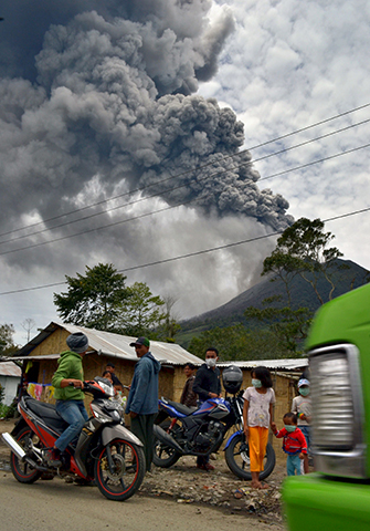 Residents leave the district of Karo as an ash cloud rises during a fresh eruption of the Mount Sinabung volcano on September 17, 2013. - Photo by AFP