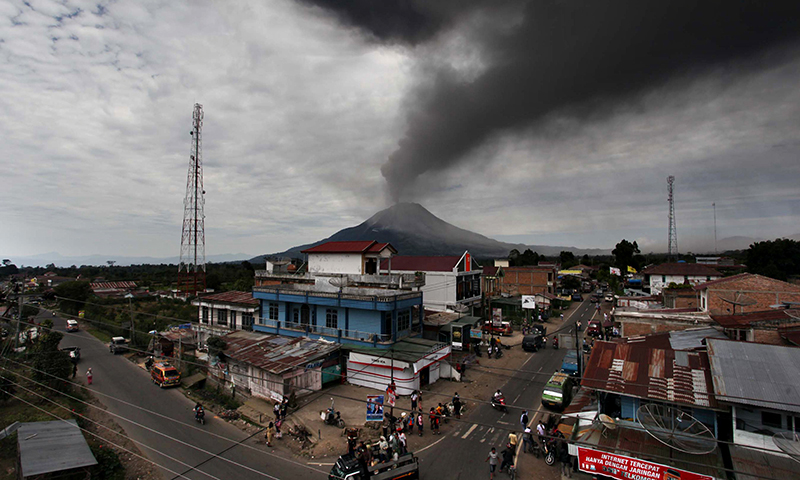 A cloud of ash rises from the crater of the Mount Sinabung volcano (back C) during a fresh eruption. - Photo by AFP