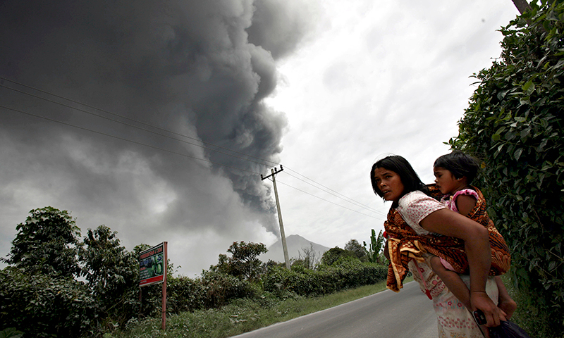 A woman and her daughter flee their home as Mount Sinabung erupts. - Photo by AP