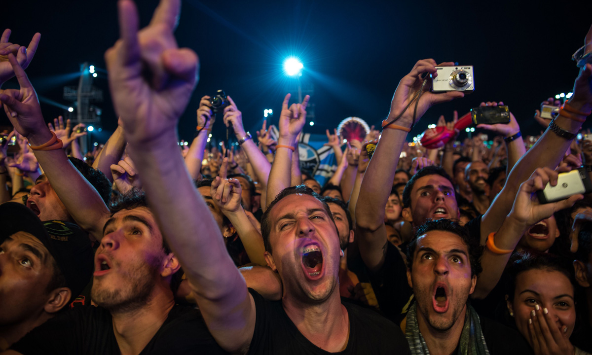 Fans emphatically cheer on as Metallica performs.