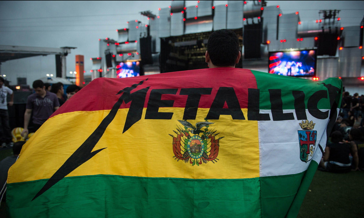 A Metallica fan is seen covering himself with a Bolivian flag during the festival in Rio de Janeiro.