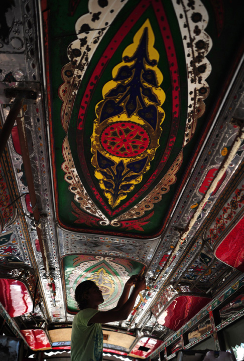A Pakistani artisan works on a design on the interior of a passenger mini bus in Karachi.