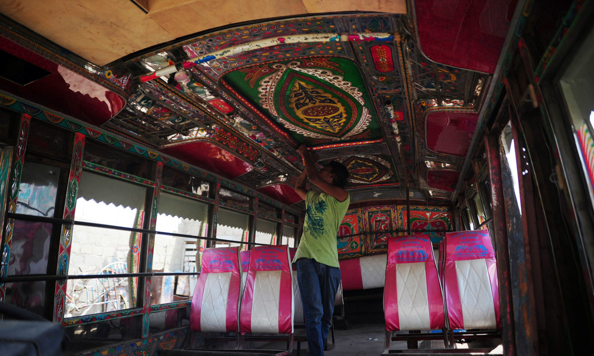 An artisan meticulously works step by step on the interior design of bus in Karachi.